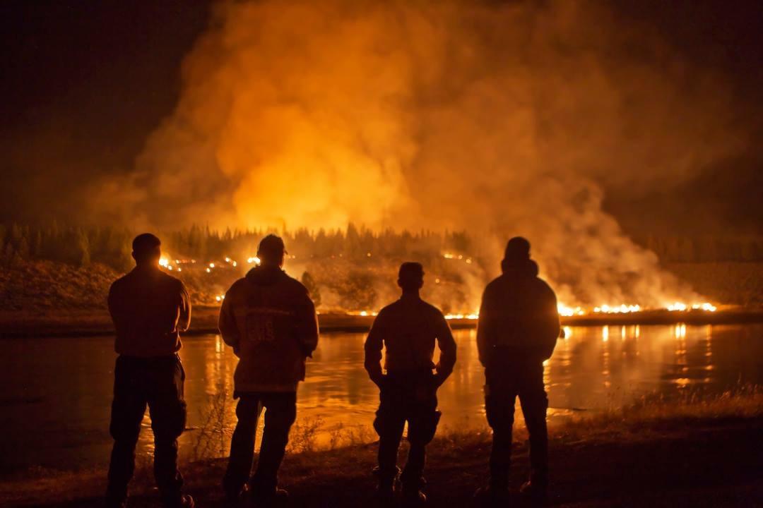 Silhouette of firemen against fire